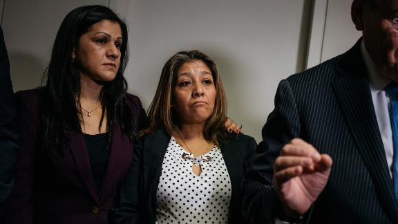 Sandra Diaz, left, and Victorina Morales,  stand behind Sen. Bob Menendez as he gives a press conference about their speaking out about being undocumented workers who formerly worked at Trump properties.
