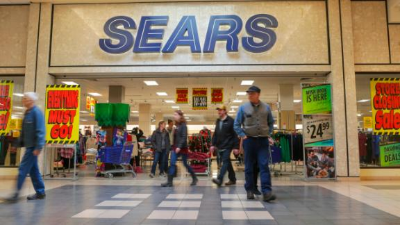 Shoppers walk by Sears department store with store closing signs at the Grand Teton Mall in Idaho Falls, Idaho on Black Friday, Nov. 23, 2018. (John Roark/The Post-Register via AP)