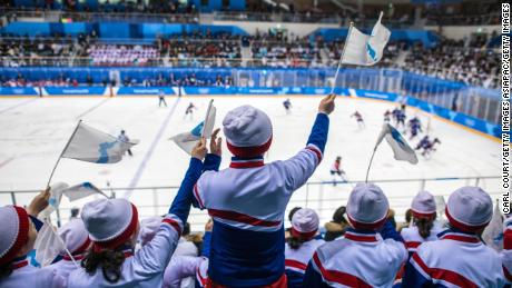 North Korean cheerleaders wave unified Korean flags.