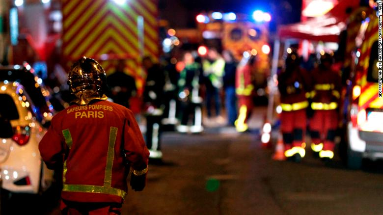 Firefighters are seen near a building that caught fire in the 16th arrondissement in Paris.