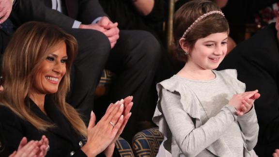 """First lady Melania Trump applauds with 10-year-old cancer survivor Grace Eline as Trump mentions Grace during his speech. Grace was 9 when she was diagnosed with germinoma, a type of brain cancer. """"At the same time, she rallied her community and raised more than $40,000 for the fight against cancer,"""" Trump said. The White House said Grace recently finished chemotherapy and today shows no evidence of the disease."""
