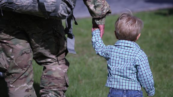 FORT DRUM, NY - MAY 17:  A father and son walk from a welcome-home ceremony for soldiers returning from Iraq on May 17, 2016 at Fort Drum, New York. More than 1,000 members of the 10th Mountain Division 1st Brigade Combat Team are returning home after a 9-month deployment in Iraq as part of Operation Inherent Resolve to train and advise Iraqi forces fighting the Islamic State. The 10th Mountain brigade was replaced in Iraq by the 101st Airborne 2nd Brigade Combat Team based at Ft. Campbell, Kentucky.  (Photo by John Moore/Getty Images)