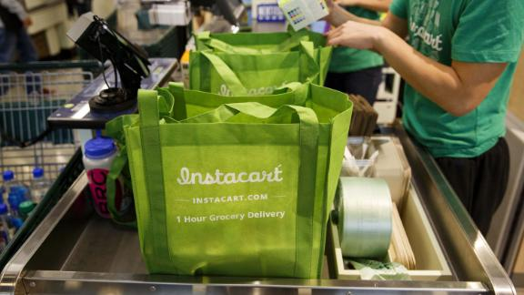InstaCart employees fulfill orders for delivery at the new Whole Foods Market store in downtown Los Angeles