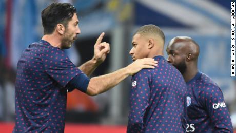 Gianluigi Buffon (L) gestures as he speaks with Paris Saint-Germain's French forward Kylian Mbappe (C) and Stanley Nsoki (R).