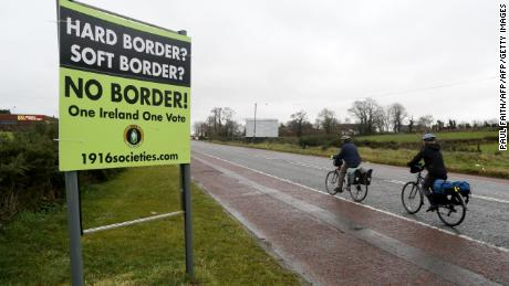"Cyclists pass a sign calling for no border to be imposed between Ireland and Northern Ireland outside Newry, Northern Ireland, on November 14, 2018 near the Irish border. - British Prime Minister Theresa May defended her anguished divorce deal with the European Union before rowdy lawmakers on Wednesday before  trying to win the backing of her splintered cabinet with the so-called ""Irish backstop"" arrangement to guard against the imposition of a hard border between Ireland and Northern Ireland one of the contentious issues, according to reports. (Photo by Paul FAITH / AFP)        (Photo credit should read PAUL FAITH/AFP/Getty Images)"