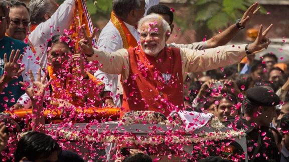 VADODRA, INDIA - APRIL 09:  Supporters throw flower petals as Bharatiya Janata Party (BJP) leader Narendra Modi rides in an open jeep on his way to file nomination papers on April 9, 2014 in Vadodra, India.  India is in the midst of a nine-phase election from April 7-May 12.  (Photo by Kevin Frayer/Getty Images)