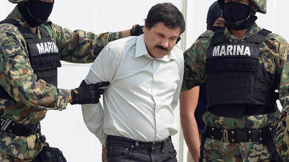 """Mexican drug trafficker Joaquin Guzman Loera aka """"el Chapo Guzman"""" (C), is escorted by marines as he is presented to the press on February 22, 2014 in Mexico City. Mexican drug lord Joaquin """"El Chapo"""" Guzman has escaped from a maximum-security prison for the second time in 14 years, sparking a massive manhunt Sunday and dealing an embarrassing blow to the government. AFP PHOTO/Alfredo Estrella        (Photo credit should read ALFREDO ESTRELLA/AFP/Getty Images)"""