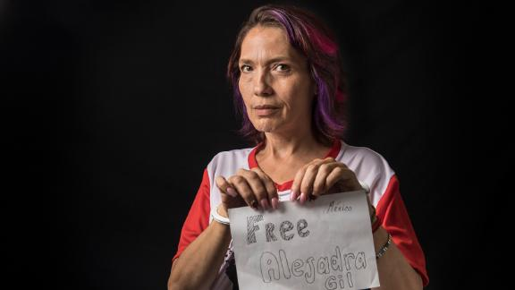 """Cynthia Navarrete, 52, holds up a sign that says """"Free Alejandra Gil,"""" her mother, who she believes was unfairly arrested for trafficking. She works as a sex worker on the streets in Mexico City and says she likes it because she can choose when to work."""