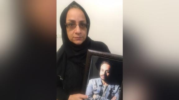 Fatemeh Malayan Nejad holds a picture of her son Sina, who was detained for protesting and died after five days in custody. Courtesy of Fatemeh Malayan Nejad/Masih Alinejad