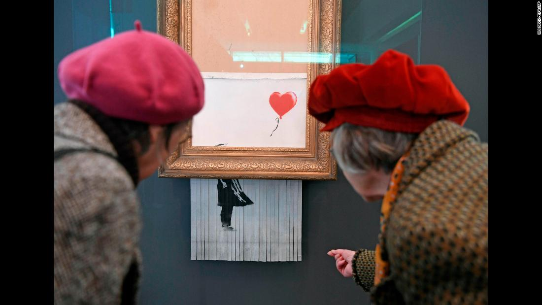 """People look at the shredded Banksy painting """"Love is in the Bin"""" at the Frieder Burda Museum in Baden-Baden, Germany, on Tuesday, February 5. The art was created when Banksy's """"Girl with Balloon"""" painting, which had just been auctioned for $1.4 million, was damaged by a paper shredder hidden inside the frame."""