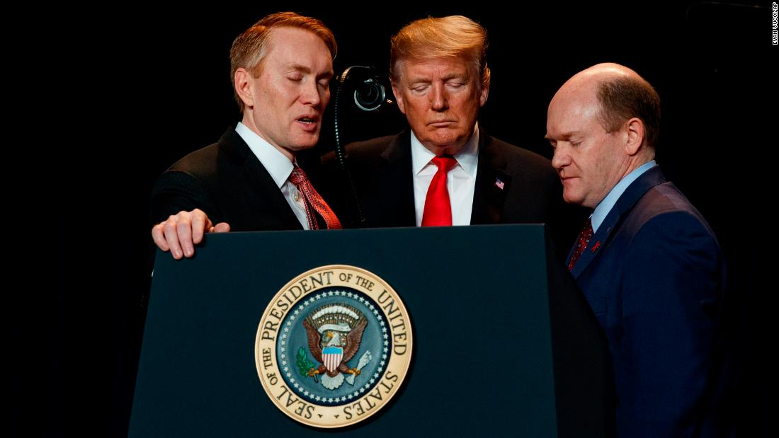 From left, US Rep. James Lankford, President Donald Trump and US Sen. Chris Coons pray during the National Prayer Breakfast in Washington on Thursday, February 7. The multi-faith breakfast, first organized in 1953, included lawmakers and religious leaders from about 70 countries.