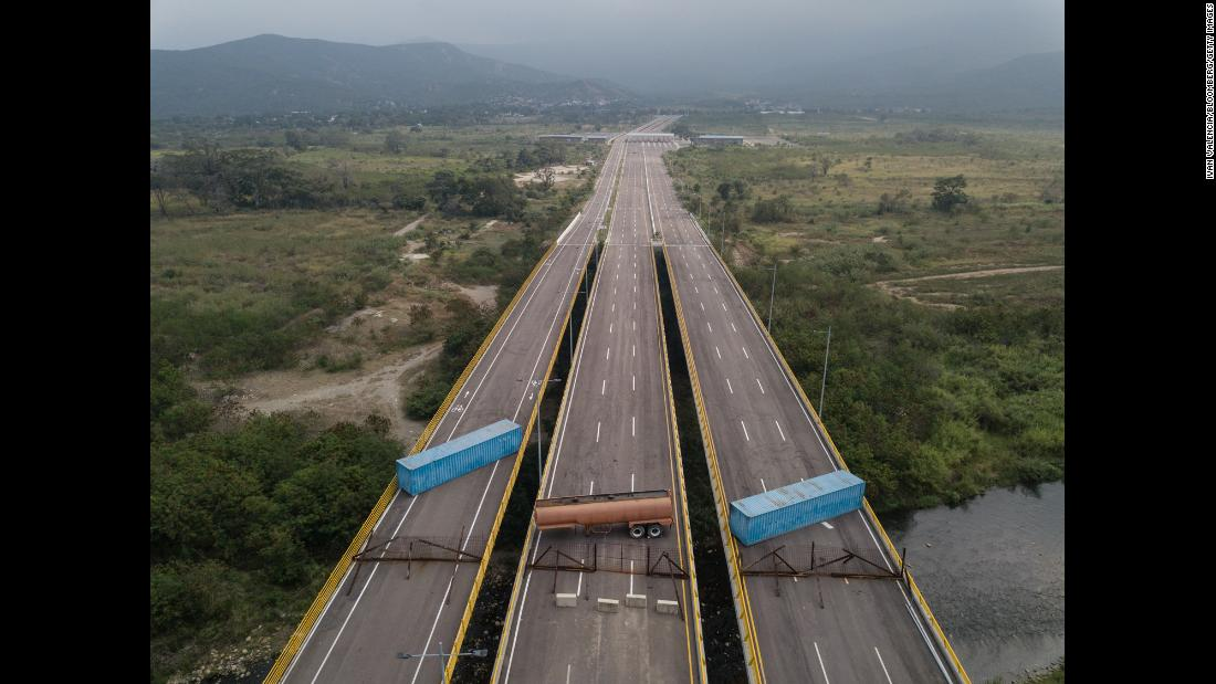 Shipping containers and a gas tank obstruct bridge lanes leading from Cucuta, Colombia, to Venezuela on Wednesday, February 6. The government of embattled Venezuelan President Nicolas Maduro has blocked aid deliveries amid rising tensions over opposition plans to bring humanitarian aid into the country.
