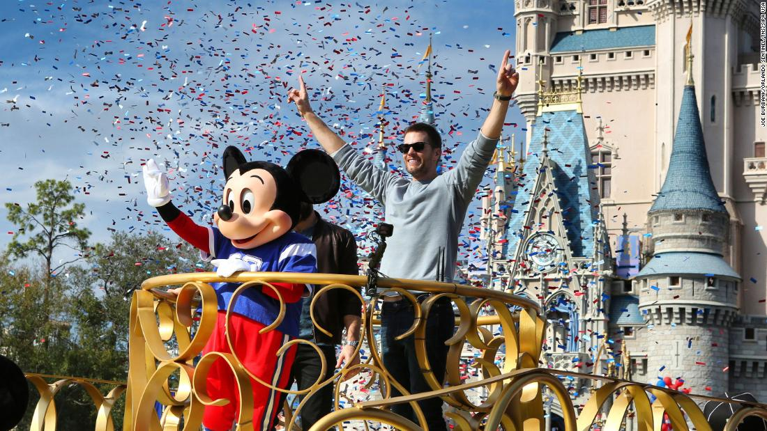 Super Bowl-winning quarterback Tom Brady celebrates with Mickey Mouse during a victory parade at Walt Disney World in Florida on Monday, February 4.