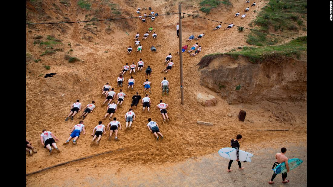 High school seniors preparing to join the Israeli military crawl along sand dunes at a privately run training camp in Herzliya, Israel, on Friday, February 1.