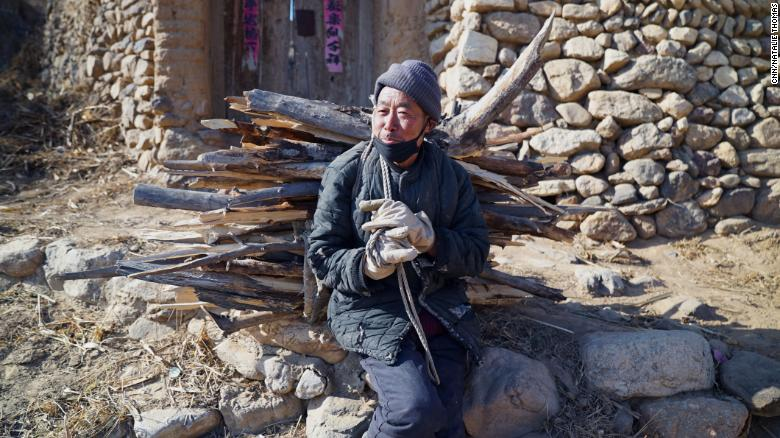 68-year-old Qin Taixiao gathers two bundles of wood every day from a nearby forest to save on heating costs.