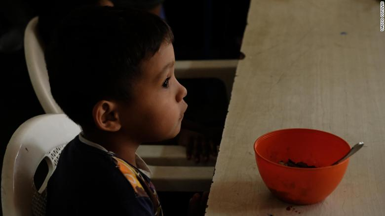 Imael, 5, with a bowl of rice and beans, his only meal of the day.