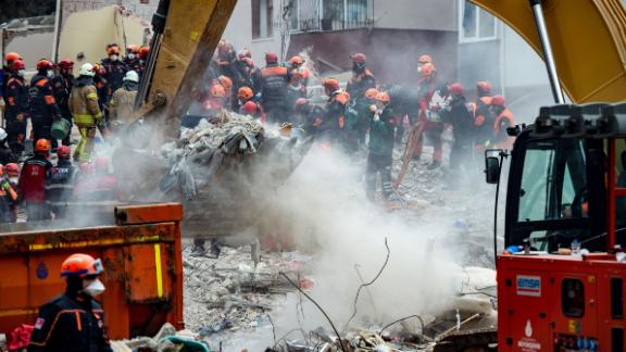 Rescue workers are seen Thursday searching the rubble of the residential building.