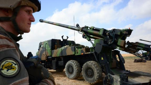 """A French soldier engaged in the """"Operation Chammal"""", the French military operation within """"Operation Inherent Resolve"""", the international coalition against the Islamic State (IS) group, stands guard in front of a wheeled 155 mm gun-howitzer CAESAR system (trucks equipped with an artillery system), on February 9, 2019, near Al-Qaim, a few kilometres away from the last scrap of territory held by IS in eastern Syria. - The US-backed Syrian Democratic Forces said on February 9, 2019 it had begun the """"final battle"""" to oust the Islamic State group from the last scrap of territory it holds in eastern Syria. (Photo by Daphné BENOIT / AFP)        (Photo credit should read DAPHNE BENOIT/AFP/Getty Images)"""
