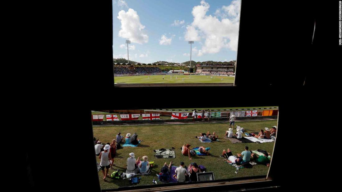 Cricket fans are seen from behind a scoreboard in St. Lucia's National Cricket Stadium on Saturday, February 9.