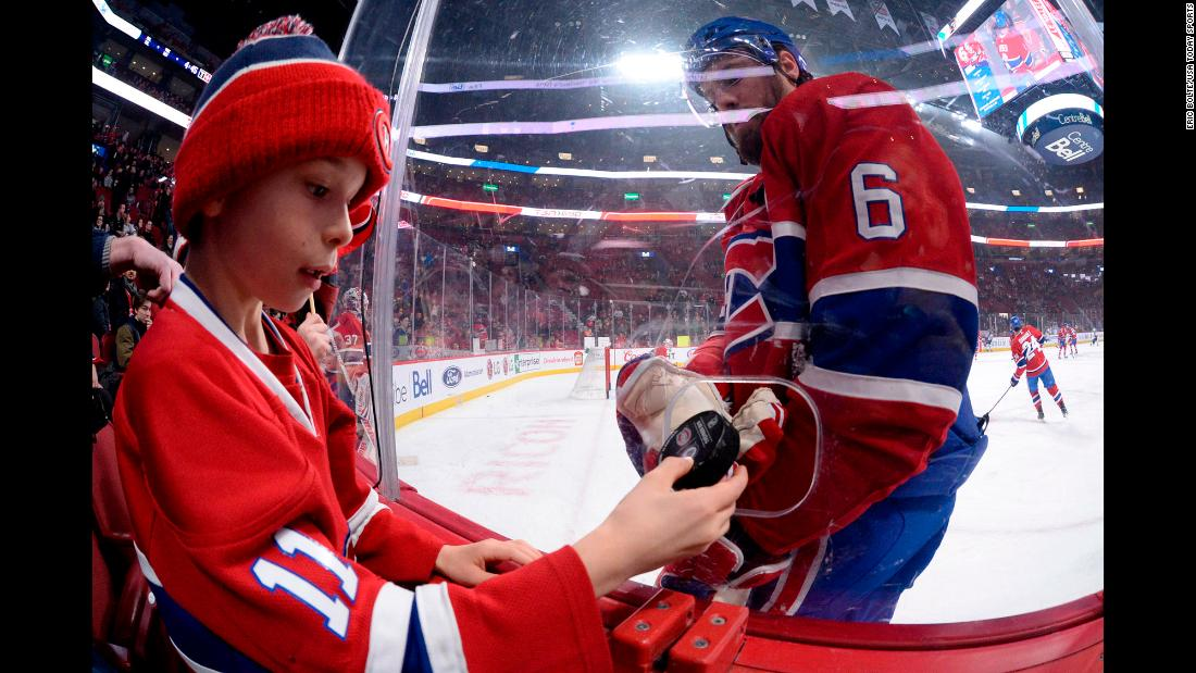 Montreal captain Shea Weber gives a puck to a young fan before an NHL game on Thursday, February 7.