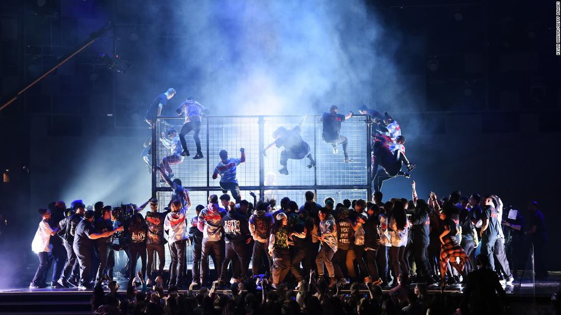 "Performers climb a cage that Travis Scott <a href=""https://www.cnn.com/entertainment/live-news/grammys-2019/h_10c433737897cbc453a9562e79823b17"" target=""_blank"">was rapping behind.</a>"