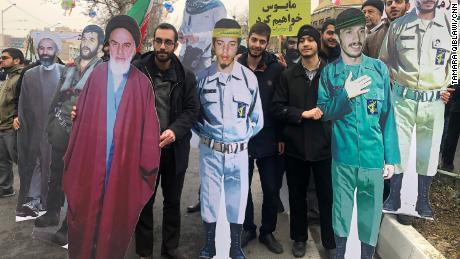Protesters carry life-sized cardboard images of iconic revolutionary figures, including Supreme Leader Rouhallah Khomeini.