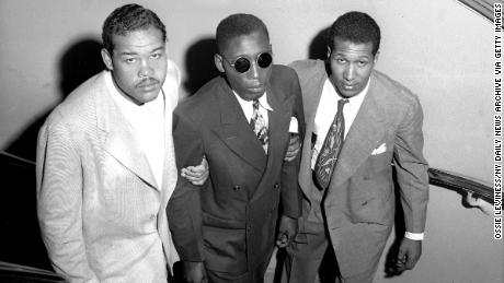Boxing champion Joe Louis (left) and Neil Scott guide Isaac Woodard up stairs at Hotel Theresa.