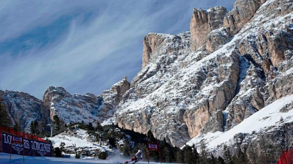A female skier competes against the domineering backdrop of Cortina