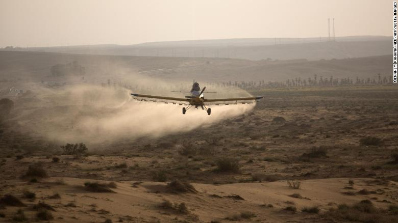 A light plane sprays pesticides on a hill in the Negev Desert near the Egyptian border.