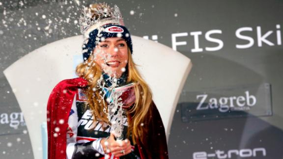 Mikaela Shiffrin celebrates with champagne and a crown after winning the women