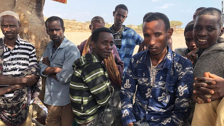 A group of men wait for smugglers to arrive to take them across the Bab al-Mandeb Strait to Yemen.