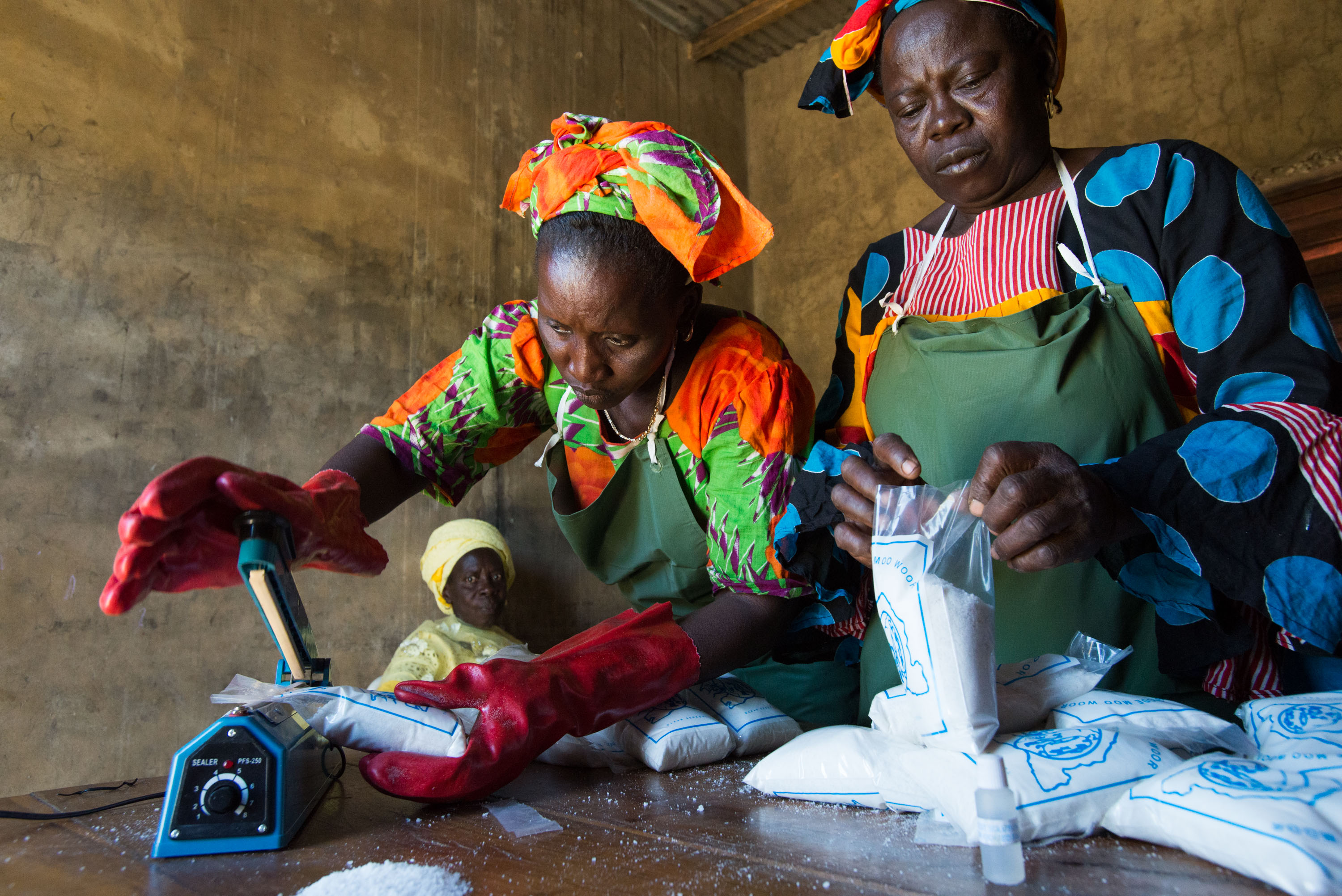 Ndeye Faye, top left, and Seynabou Diouf, right, test salt for iodine content before sealing it in plastic bags, while Fatou Sarr, bottom left, looks on. Marie Diouf employs the women in her micro-business producing and packaging iodized salt.
