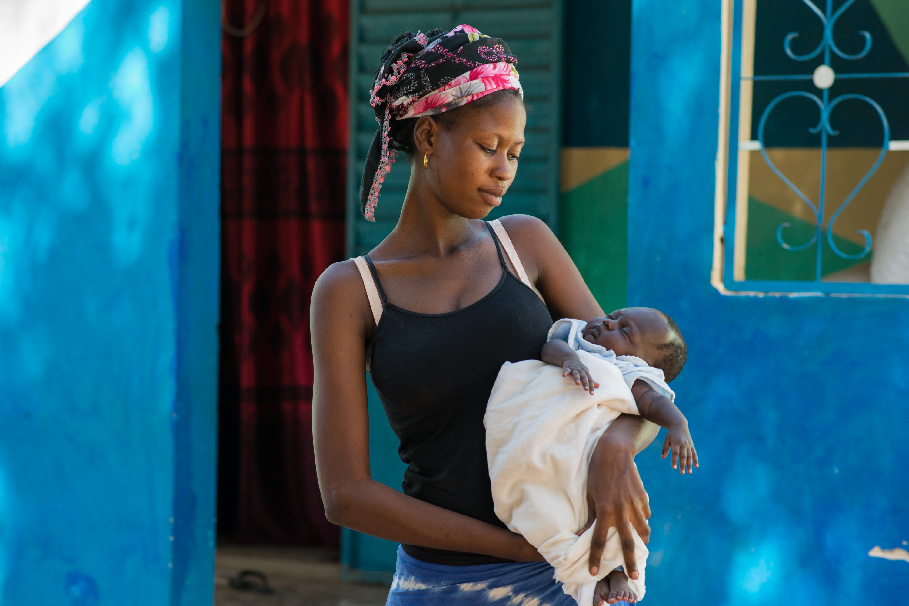 Aby Faye, 17, holds her two month old baby, Sokhna. Faye says she was aware of the importance of iodine during pregnancy thanks to Marie's campaigning in their village.