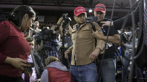A man is restrained after he entered the media area during a Trump rally in El Paso.