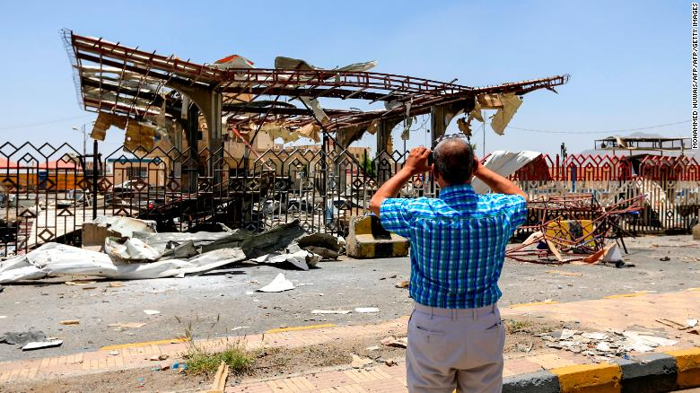 A Yemeni man takes a picture of a destroyed petrol station that was hit by an airstrike in Yemen's capital Sanaa on May 27, 2018.