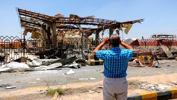 A Yemeni man uses a cell phone to take a picture of a destroyed petrol station that was hit by an airstrike in the capital Sanaa on May 27, 2018.