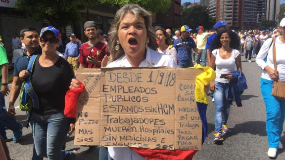 """An anti-Maduro protester carries a cardboard poster which reads: """"Since 1/9/18 public servants have gone without health insurance. Workers are dying. Hospitals don't have medicines or supplies. SOS"""""""