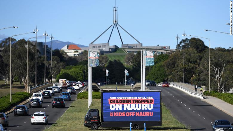 A billboard protesting the detention of children on Nauru sits outside of  Parliament House on November 26 in Canberra.