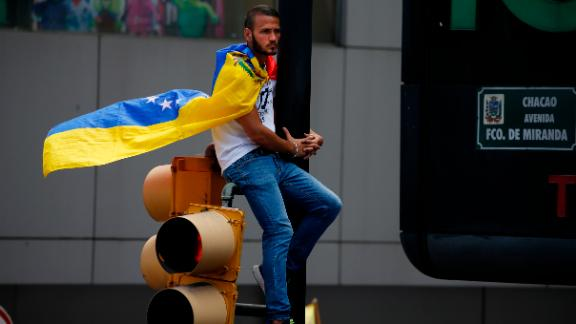 A man wearing a Venezuelan flag sits on a traffic light during the demonstration in Caracas on February 12.