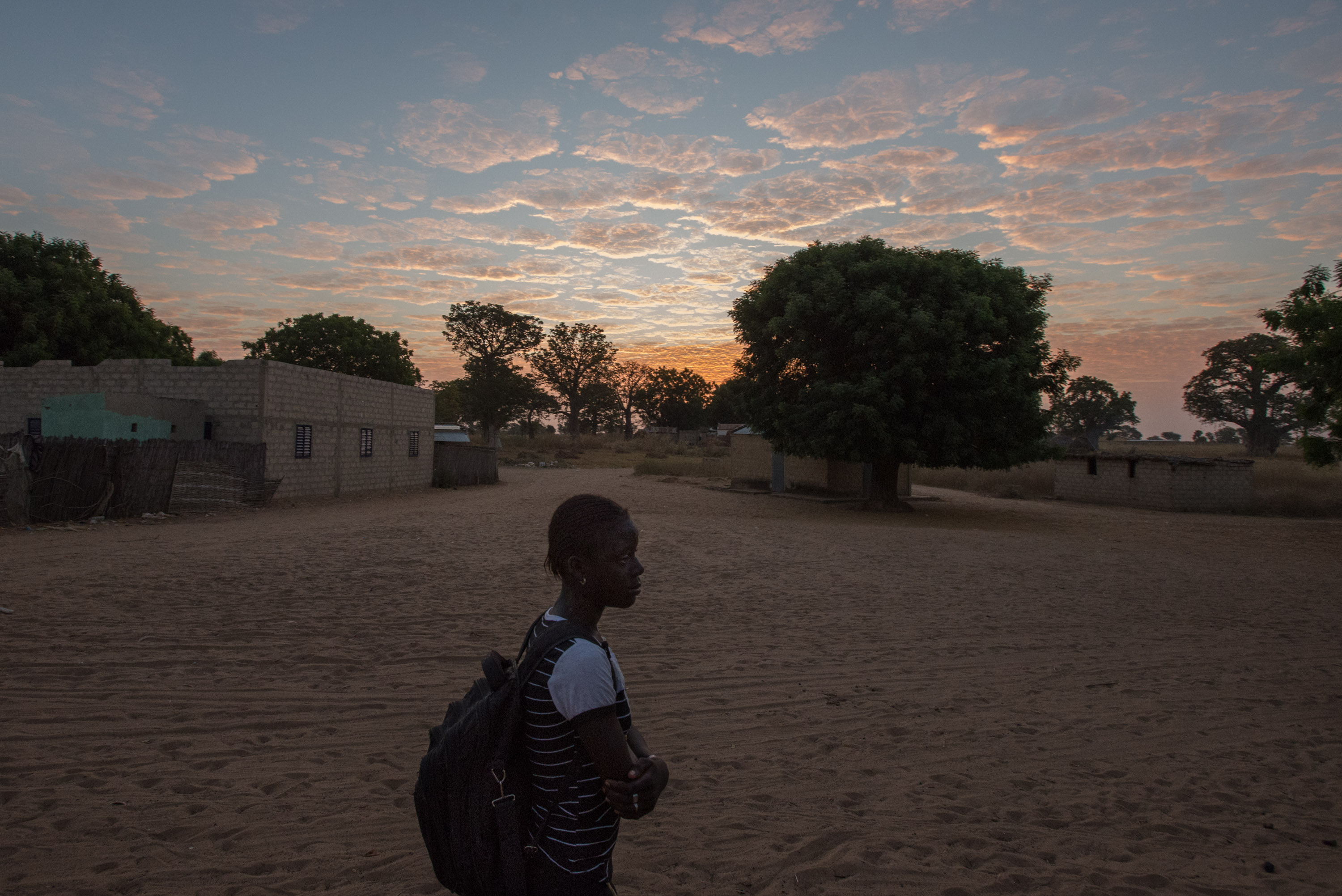 Marie's daughter Fatou, backpack in tow, sets off early one morning for school.