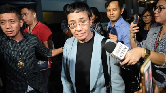 "Philippine journalist Maria Ressa (C) is surrounded by the press as she is escorted by a National Bureau Investigation (NBI) agent (L) at the NBI headquarters after her arrest in Manila on February 13, 2019. - Ressa, who has repeatedly clashed with President Rodrigo Duterte, was arrested in her Manila office on February 13 in what rights advocates called an act of ""persecution"". (Photo by TED ALJIBE / AFP)        (Photo credit should read TED ALJIBE/AFP/Getty Images)"