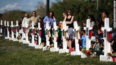 PARKLAND, FL - FEBRUARY 18: People visit a makeshift memorial in front of the Marjory Stoneman Douglas High School where 17 people were killed on February 14, on February 18, 2018 in Parkland, Florida. Police arrested 19-year-old former student Nikolas Cruz for killing 17 people at the high school.  (Photo by Mark Wilson/Getty Images)