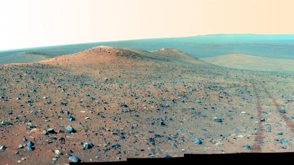 Oppy's panoramic camera gathered this mosaic in 2014 of Wdowiak Ridge, as well as the rover's tracks to the right. This is about 70 degrees from north/northwest to east/northeast, showing the 500-feet ridge that rises 40 feet tall.