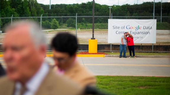 Workers take a selfie at the site of a proposed $300 million expansion of Google's data center operations as Georgia Gov. Nathan Deal, left, talks to reporters following a ceremony Tuesday, June 2, 2015, in Lithia Springs, Ga. The new facility will be located next to the existing data center, one of 13 in the world, and will add 25 jobs to the 350 employees currently employed there by Google. The new facility is scheduled to be operational by the end of 2016. (AP Photo/David Goldman)