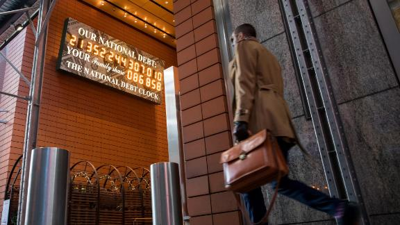 A pedestrian passes the National Debt Clock on West 43rd Street in New York, U.S., on Friday, Jan. 11, 2019. U.S. stocks dipped Friday as a decline in energy shares and mounting concerns about the ongoing government shutdown overwhelmed strength among carmakers following an optimistic earnings outlook from General Motors Co. Photographer: Michael Nagle/Bloomberg via Getty Images