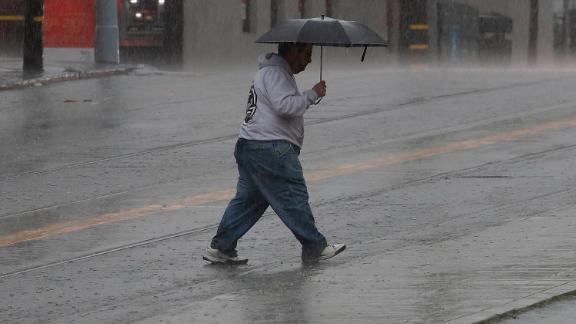 A man carries an umbrella as he crosses the street in San Francisco, Wednesday, Feb. 13, 2019. Rain, snow and wind swept into California on Wednesday, flooding roadways, toppling trees and disrupting travel while bringing renewed threats of mud and debris flows from the state's huge wildfire burn scars. (AP Photo/Jeff Chiu)