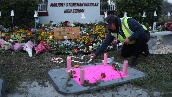 PARKLAND, FLORIDA - FEBRUARY 14: Wendy Behrend, a school crossing guard who was on duty one year ago when a shooter opened fire in Marjory Stoneman Douglas High School pays her respects at a memorial setup for those killed on February 14, 2019 in Parkland,  Florida. A year ago on Feb. 14th at Marjory Stoneman Douglas High School 14 students and three staff members were killed during the mass shooting. (Photo by Joe Raedle/Getty Images)