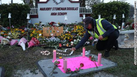 PARKLAND, FLORIDA - FEBRUARY 14: Wendy Behrend, a school crossing guard who was on duty one year ago when a shooter opened fire in Marjory Stoneman Douglas High School pays her respects at a memorial setup for those killed on February 14, 2019 in Parkland,  Florida.