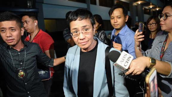 """Philippine journalist Maria Ressa (C) is surrounded by the press as she is escorted by a National Bureau Investigation (NBI) agent (L) at the NBI headquarters after her arrest in Manila on February 13, 2019. - Ressa, who has repeatedly clashed with President Rodrigo Duterte, was arrested in her Manila office on February 13 in what rights advocates called an act of """"persecution"""". (Photo by TED ALJIBE / AFP)        (Photo credit should read TED ALJIBE/AFP/Getty Images)"""