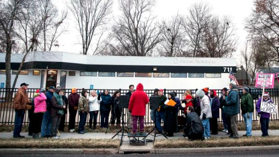 Anti-abortion advocate Joanne Schrader of Fulton (in red) speaks during a news conference organized by fellow anti-abortion advocates accusing Planned Parenthood facilities of being unsafe, while Planned Parenthood supporters hold signs at right, outside the Planned Parenthood Columbia Health Center on Monday, Dec. 12, 2016 in Columbia, Mo. The news conference was one of five held simultaneously outside Planned Parenthood locations across the state in which anti-abortion advocates argued that the number of ambulance calls to the St. Louis clinic since 2009 was cause for concern. (Timothy Tai/Columbia Daily Tribune via AP)